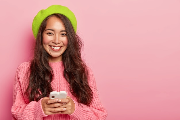 Uśmiechnięta brunetka kobieta z długimi włosami, nosi jasnozielony beret i duży sweter, trzyma nowoczesny telefon komórkowy podłączony do bezprzewodowego internetu