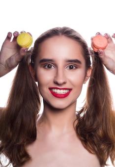 Uśmiechnięta brunetka kobieta z jasny makijaż gospodarstwa słodkie makaroniki. studio strzał na białym tle