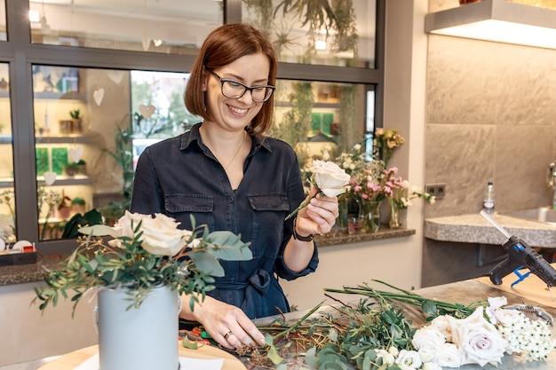 Uśmiechnięta brunetka kobieta zbieranie pudełko kwiat. kwiaciarz. warsztaty florystyczne. koncepcja nauczania klasy mistrzowskiej.