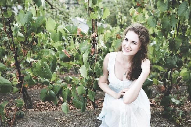 Uśmiechnięta brunetka kręcone włosy w winnicy