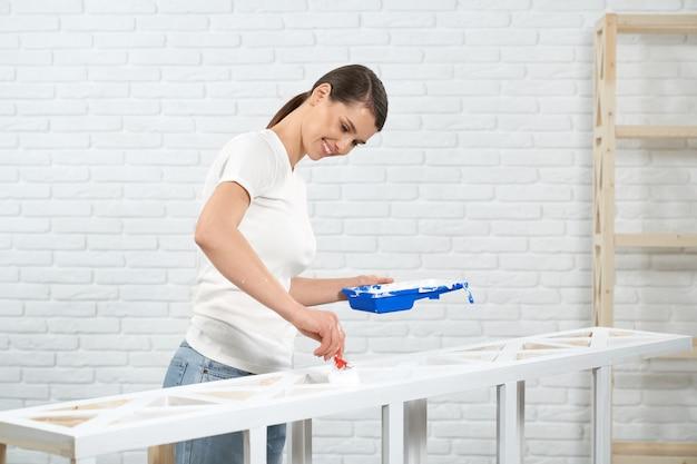 Uśmiechnięta brunetka malująca drewniany stojak w kolorze białym