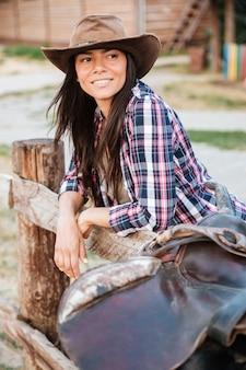 Uśmiechnięta brunetka młoda kobieta cowgirl opierając się na płocie w wiosce i odwracając wzrok
