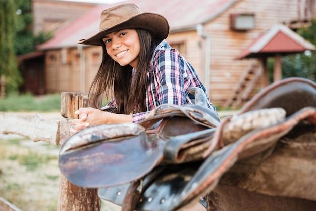 Uśmiechnięta brunetka młoda kobieta cowgirl opierając się na płocie w wiosce