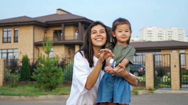 Uśmiechnięta brunetka młoda kobieta i mała azjatka chwalą się kluczami do nowego mieszkania na tle budynków mieszkalnych na zbliżenie ulicy miasta