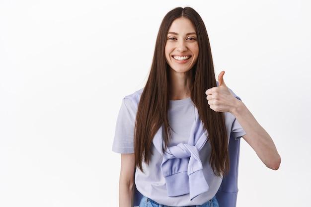Uśmiechnięta brunetka pokazuje kciuk w górę, kiwa głową z aprobatą, popiera dobry wybór, chwali świetną robotę, znakomitą rzecz, stoi nad białą ścianą