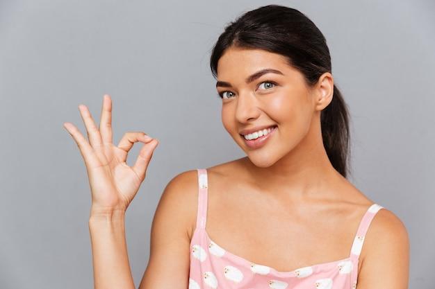 Uśmiechnięta brunetka pokazuje znak ok na szarej ścianie