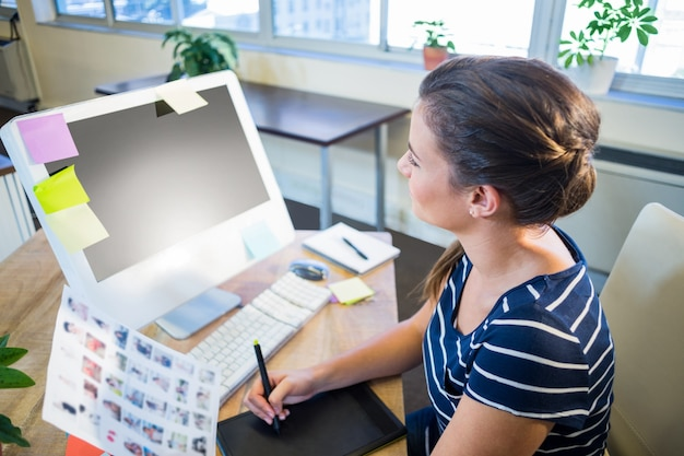 Uśmiechnięta brunetka pracuje z fotografiami i digitizer