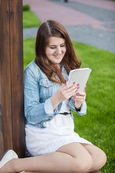 Uśmiechnięta brunetka studentka czytająca książkę na tablecie w parku na trawie