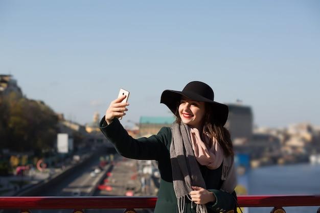 Uśmiechnięta brunetka turystka w kapeluszu robi zdjęcie selfie w słoneczny dzień w kijowie
