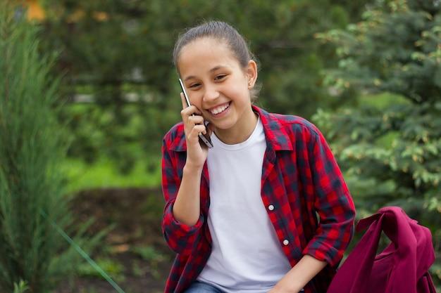 Uśmiechnięta brunetka uczennica siedzi w parku i komunikuje się przez telefon komórkowy