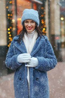 Uśmiechnięta brunetka w płaszczu spacerująca po mieście w śnieżną pogodę