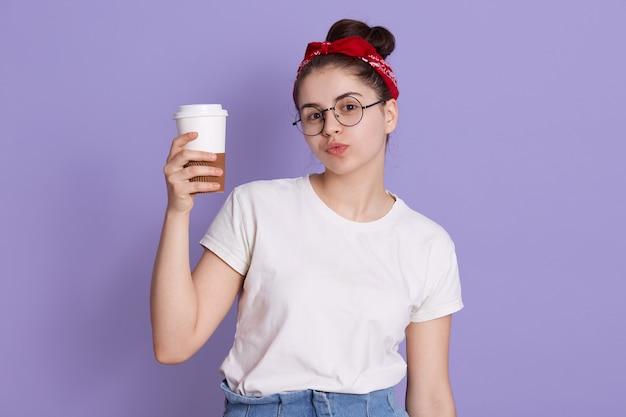 Uśmiechnięta brunetka z kępką i czerwoną opaską na sobie białą koszulkę na co dzień