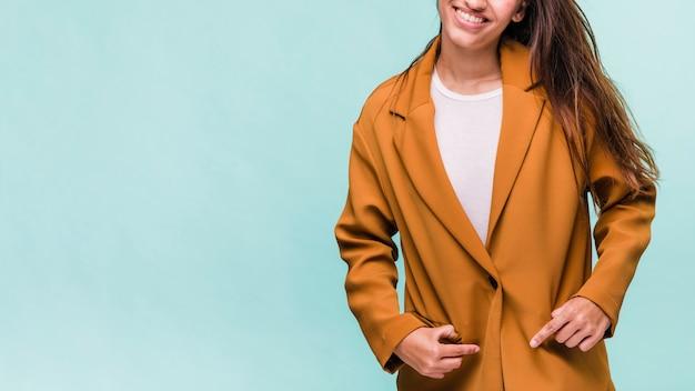 Uśmiechnięta brunetki dziewczyna pozuje z żakietem