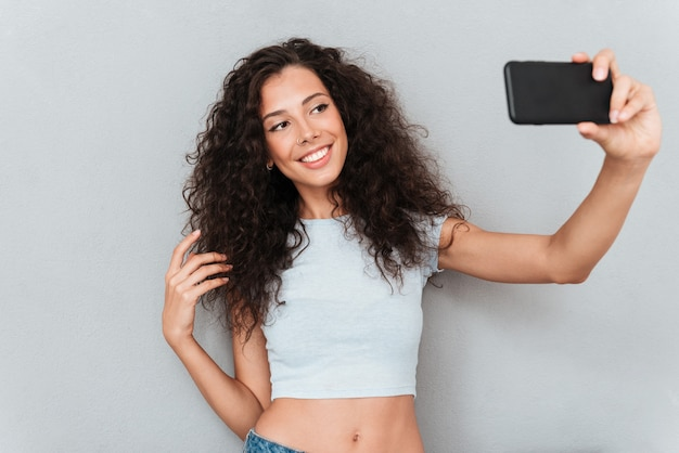Uśmiechnięta brunetki kobieta robi selfie na telefonie