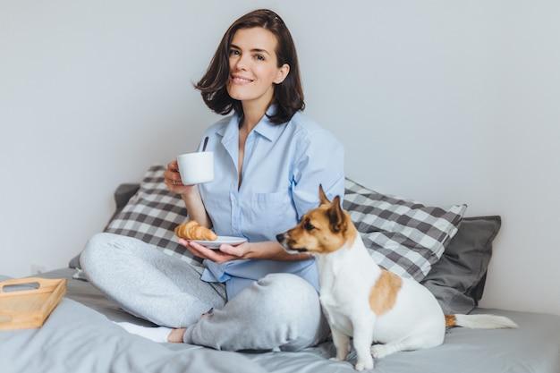 Uśmiechnięta brunetki kobieta trzyma filiżankę gorącego napoju i wyśmienicie rogalika, je śniadanie w ranku