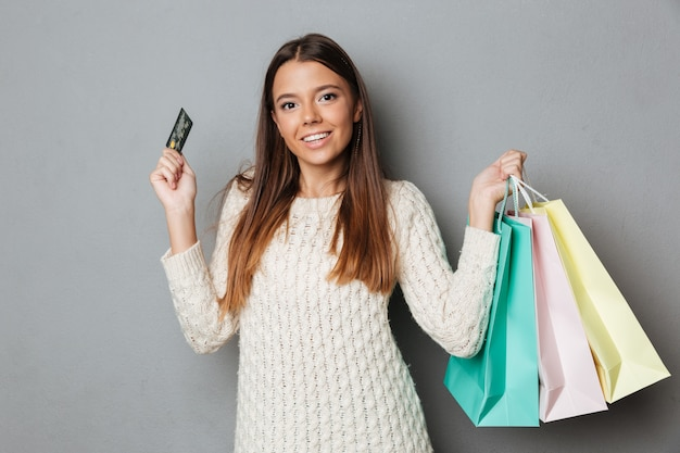 Uśmiechnięta brunetki kobieta w puloweru mienia pakunkach i kredytowej karcie