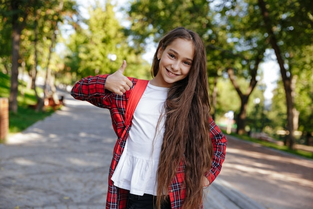 Uśmiechnięta brunetki młoda dziewczyna pozuje w parku i pokazuje kciuk up