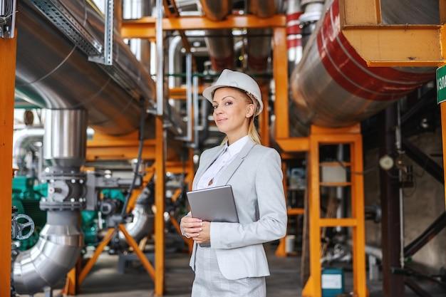 Uśmiechnięta ceo kobieta w formalnym stroju, z hełmem ochronnym na głowie trzymając tablet i stojąca w ciepłowni