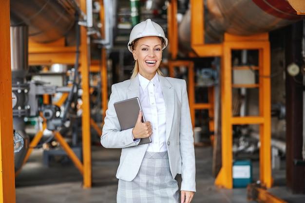 Uśmiechnięta ceo kobieta w stroju wizytowym, z hełmem ochronnym na głowie trzymając tablet i stojąca w ciepłowni.