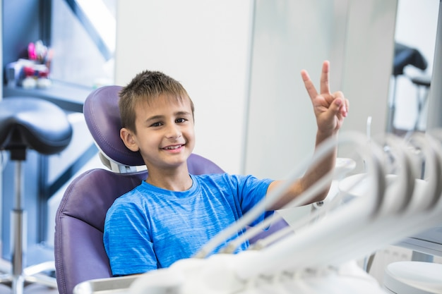 Uśmiechnięta chłopiec gestykuluje zwycięstwo znaka w klinice
