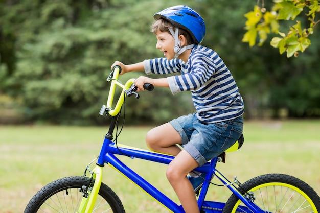 Uśmiechnięta chłopiec jedzie bicykl