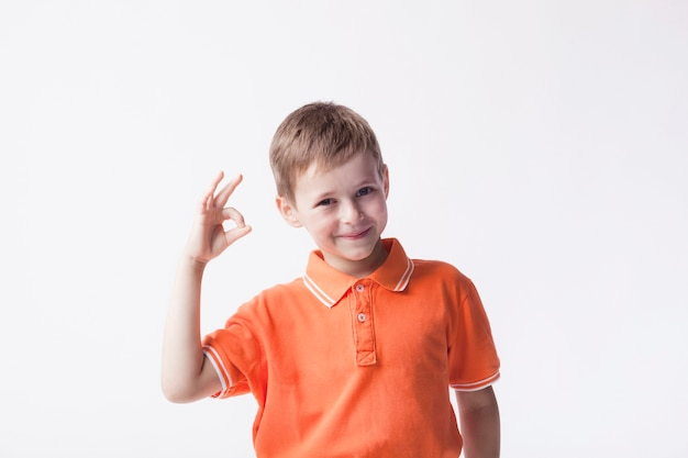 Uśmiechnięta chłopiec jest ubranym pomarańczową koszulkę gestykuluje ok szyldowego na białym tle