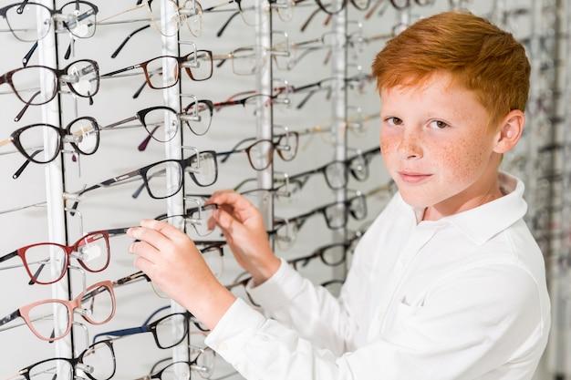 Uśmiechnięta chłopiec patrzeje kamerę podczas gdy usuwający eyeglasses pokazu frontowego stojaka