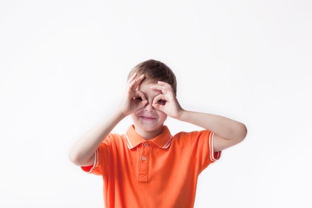 Uśmiechnięta chłopiec patrzeje przez ok ręka gesta na białym tle