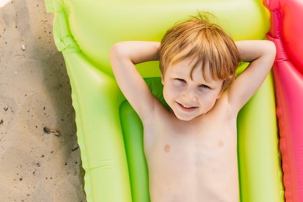 Uśmiechnięta chłopiec relaksuje na lotniczej materac na plaży w wakacje