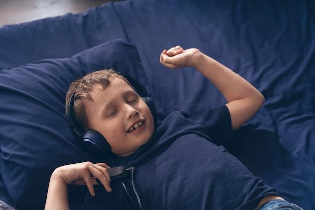 Uśmiechnięta chłopiec słucha muzyka w hełmofonach, kłama w łóżku