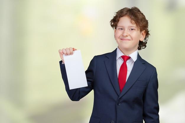 Uśmiechnięta chłopiec trzyma pustego papier