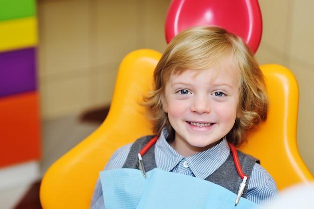 Uśmiechnięta chłopiec z blond kędzierzawym włosy w stomatologicznym krześle.