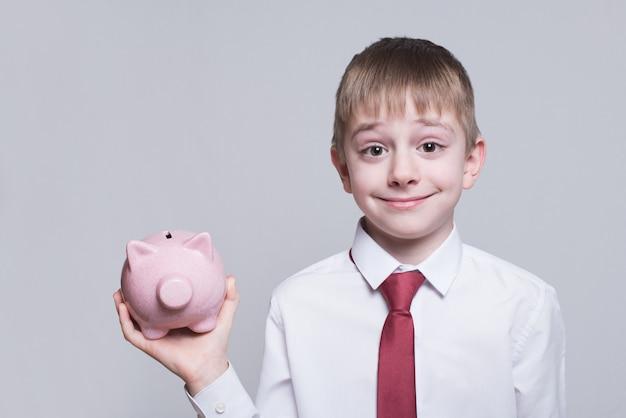 Uśmiechnięta chłopiec z różową prosiątko banka świnią w jego rękach. pomysł na biznes.