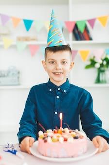 Uśmiechnięta chłopiec z urodzinowym tortem