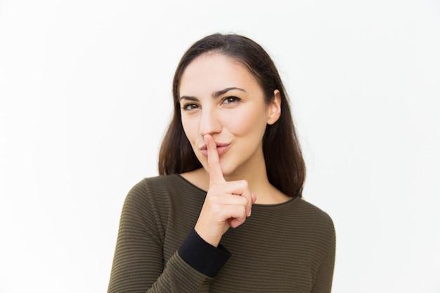 Uśmiechnięta chytra łacińska kobieta stosuje palec przy usta