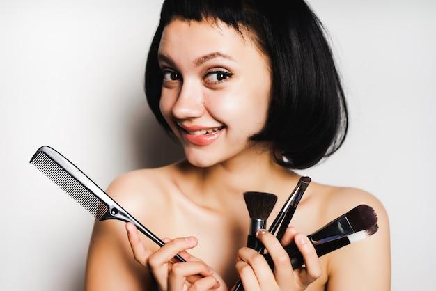 Uśmiechnięta ciemnowłosa dziewczyna patrząca w kamerę i trzymająca grzebień i pędzle do makijażu