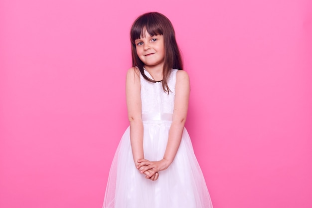 Uśmiechnięta ciemnowłosa dziewczyna ubrana w białą sukienkę, patrząc z przodu z uroczym i szczęśliwym wyrazem twarzy, jest nieco nieśmiała, pozuje odizolowana na różowej ścianie