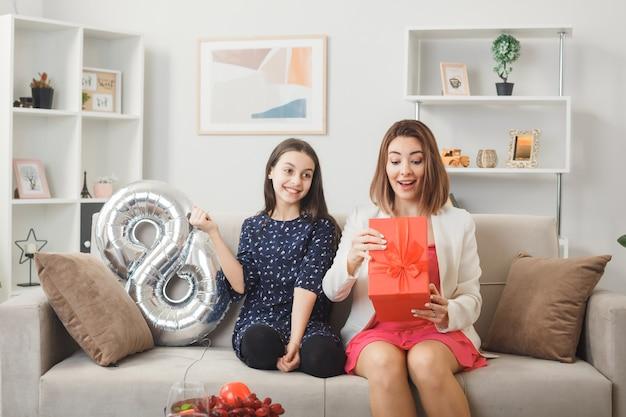Uśmiechnięta córka daje prezent zaskoczonej matce w szczęśliwy dzień kobiety siedzącej na kanapie w salonie