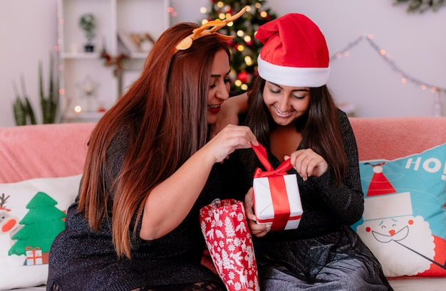 Uśmiechnięta córka i matka otwierają pudełko z prezentami dla córki siedzącej na kanapie, ciesząc się świątecznym czasem w domu