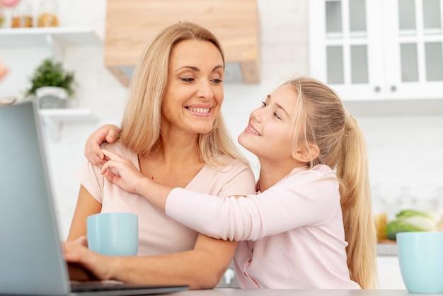 Uśmiechnięta córka obejmuje jej matki