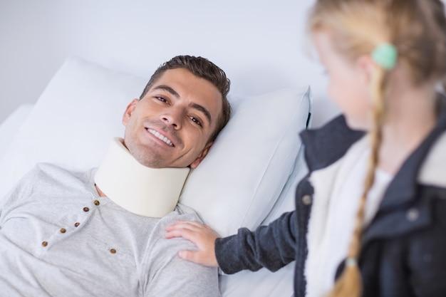 Uśmiechnięta córka pociesza jej chorego ojca