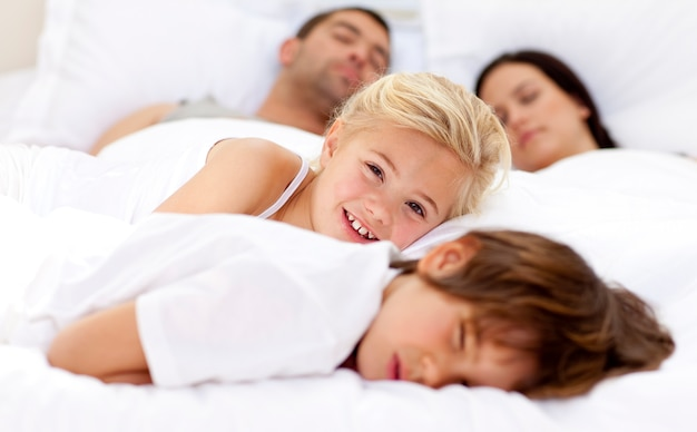 Uśmiechnięta córka relaksuje z jej bratem i rodzicami w łóżku