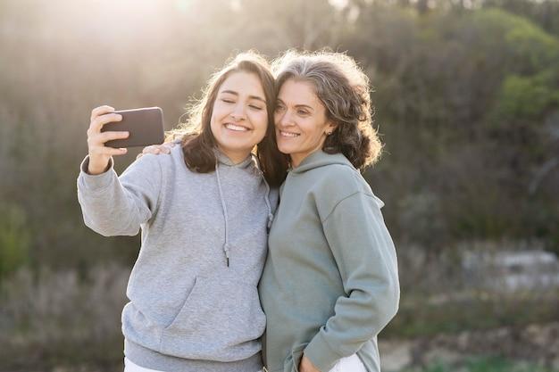 Uśmiechnięta córka robi selfie z matką na zewnątrz