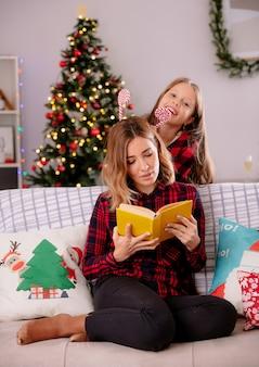 Uśmiechnięta córka trzyma candy cane stojąc za matką, czytając książkę, siedząc na kanapie i ciesząc się boże narodzenie w domu