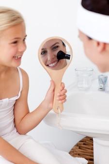 Uśmiechnięta córka trzyma lustro i macierzysty kładzenie makeup