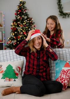 Uśmiechnięta córka wkłada czapkę mikołaja na głowę mamy siedzącej na kanapie i cieszącej się świętami w domu