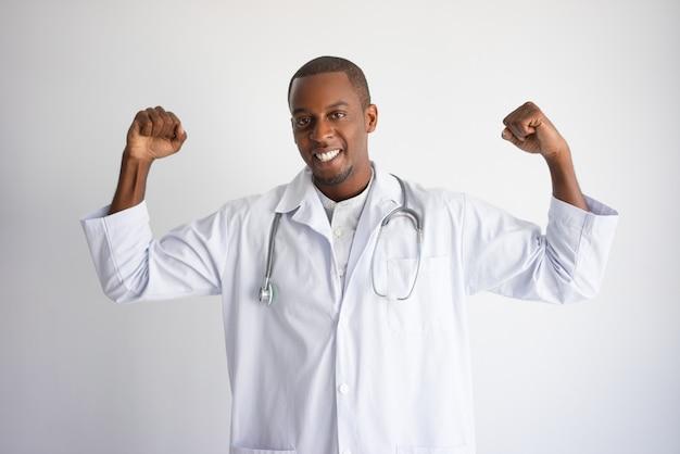 Uśmiechnięta czarna samiec lekarka pompuje pięści i świętuje sukces.