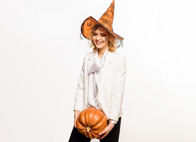 Uśmiechnięta czarownica halloween z dynią. szczęśliwa dziewczyna w kapeluszu czarownicy. 31 października.