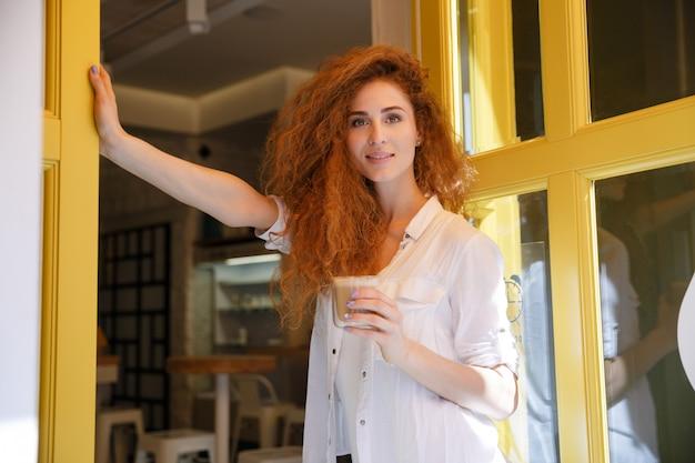 Uśmiechnięta czerwona włosiana kobieta stoi filiżankę kawy i trzyma