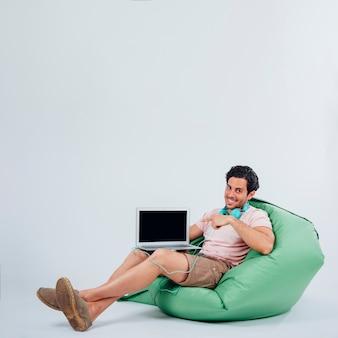 Uśmiechnięta człowiek na kanapie z laptopem